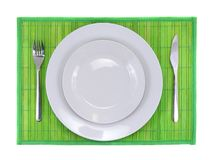 Table serving-dishware on green backdrop. Stock Image