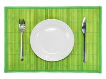 Table serving-dishware on green backdrop. Stock Photography