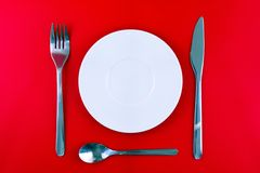 Table serving-dishware on red backdrop. Stock Photography