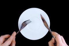 Table serving-knife, fork in hands Royalty Free Stock Images