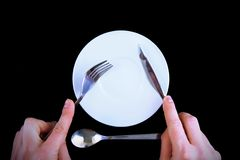 Table serving-knife, fork in hands Royalty Free Stock Photography