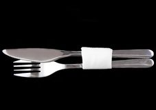 Table serving-knife,spoon,fork on colour backdrop. Stock Image
