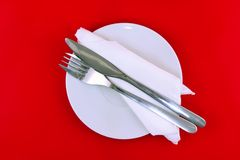 Table serving-knife,spoon,fork on red  backdrop. Stock Photos