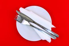 Table serving-knife,spoon,fork on red  backdrop. Royalty Free Stock Photos