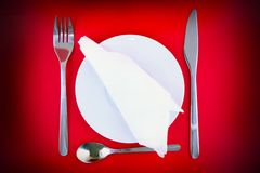 Table serving-knife,spoon,fork on red  backdrop. Royalty Free Stock Images