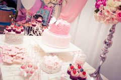 Baby girl first birthday party - luxury table. Table set for baby girl first birthday party with candy theme and flower masterpiece royalty free stock photography