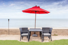 The table set, beach chairs and red umbrella with beautiful beac Stock Image