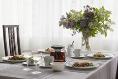 Table set for Breakfast with a bouquet of lilacs on a summer mor Stock Photography