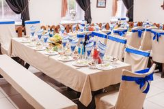 Table set for a bridal party white tablecloth and white and blue ribbons chairs royalty free stock photography