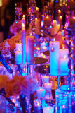 Table set with candles for a festive event, party or wedding reception, in purple light Stock Photography