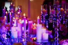 Table set with candles for a festive event, party or wedding reception, in purple light. Beautiful table set with candles for a festive event, party or wedding Royalty Free Stock Image