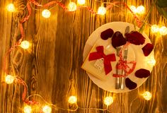 Table set for celebration Valentine`s Day. Wooden place setting with red heart and glittering lights . Table set for celebration Valentine`s Day. Wooden table stock images