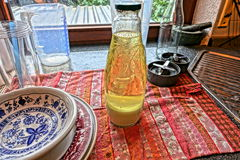 Table set with china and bottle of Vitamin C. Table next to window set with blue, red and white china on colorful place mat with bottle of yellow Vitamin C Stock Photography