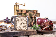 Table set with cup of tea and coffee grinder Royalty Free Stock Image