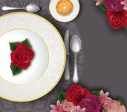 Table set, decorated with gold plate, cutlery and flowers Stock Photo