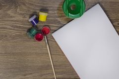 On the table is a set for drawing: a brush, gouache and a white sheet of paper. On a brush red paint.  stock photos