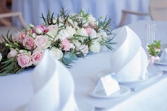 Table set for an event party or wedding reception. Large floral arrangement of roses and peonies Royalty Free Stock Images