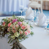 Table set for an event party or wedding reception. Large floral arrangement of roses and peonies Stock Photography