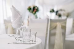 Table set for an event party or wedding reception on white tablecloth. White soft background with tables and flowers.  royalty free stock images