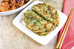 Table set for Korean Green Pancakes and barbequed pork. Horizontal photo of Korean green onion pancakes in plate, chopsticks on cloth napkin, and spicy barbequed stock image