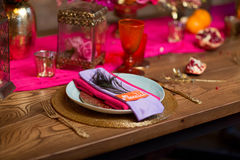 A table set with plate decorate in purple and pink. A wooden table set with plate decorate in purple and pink Stock Images