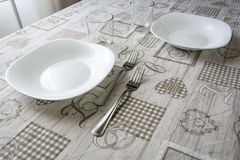 Table set with plates, glasses, cutlery and tablecloth royalty free stock images