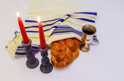Table set for Shabbat with lighted candles, challah bread and wine. A table set for Shabbat with lighted candles, challah bread and wine stock photo