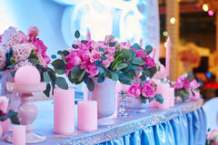 Table set for wedding reception with candles and flower bouquets Stock Photos