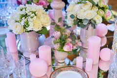 Table set for wedding reception with candles and flower bouquets Stock Images