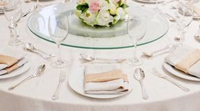 The table is set for a western style dinner with round glass on Stock Image