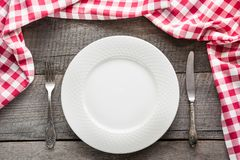 Table set with white plate with knife and fork with red napkin around . Stock Images