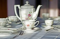 Fine porcelaine cup, jug and silver cutlery on table. Table set with white tablecloth and china. Fine porcelaine coffee cup, jug and silver cutlery closeup in Stock Photo