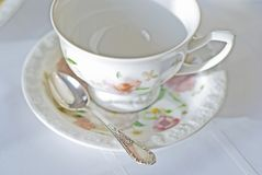 Fine porcelaine cup and silver spoon on table. Table set with white tablecloth and china. Fine porcelaine coffee cup and silver spoon closeup in  short focus Royalty Free Stock Photo