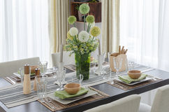 Table set on wooden dinning table with flower in glass vase Stock Images