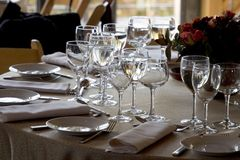 Table Setting #1. A fancy table setting awaits the guests. Focus is on the forground plate and glasses stock image