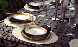 Table setting. On a patio table with plates and martini glasses Stock Images