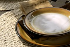 Table setting. On a patio table with plates and place mats Royalty Free Stock Images