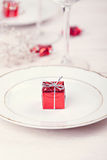 Table setting. Festive table setting with red gift on plate Royalty Free Stock Photos