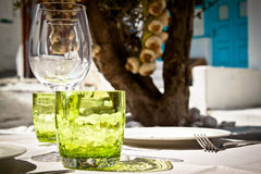Table setting for al fresco dining. In a picturesque village street with olive tree and garlic in the background Royalty Free Stock Images
