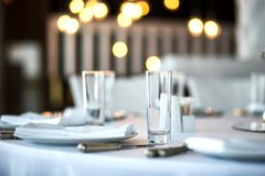 Free Table Setting At A Restaurant. Clean Glass Cup Close Up. Details Of The Banquet Table. On The Background Blur Are Burning Garlands Royalty Free Stock Images - 159240339