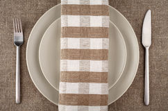 Table setting. Beige plate, fork, knife and beige linen napkin and tablecloth. Stock Photo