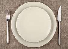 Table setting. Beige plate, fork, knife and beige linen tablecloth. Stock Photos