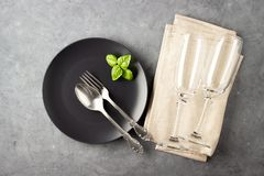 Table setting with black matte plate, wine glass and cutlery. View from above over gray concrete background stock photos