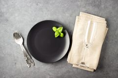 Table setting with black matte plate, wine glass and cutlery. View from above over gray concrete background stock photo
