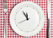 Table setting with blank clock on plate, time concept. Blank clock on plate, time concept stock image