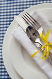 Table setting with blue checkered tablecloth and white napkin Royalty Free Stock Photo