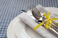 Table setting with blue checkered tablecloth and white napkin Royalty Free Stock Image