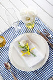 Table setting with blue checkered tablecloth, white napkin and y Royalty Free Stock Photos