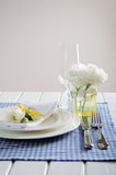 Table setting with blue checkered tablecloth, white napkin and y Royalty Free Stock Images