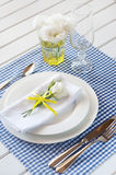 Table setting with blue checkered tablecloth, white napkin and y Stock Photo